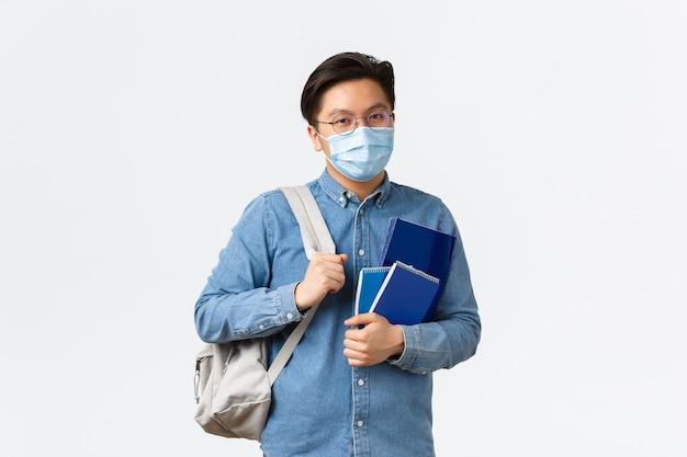 Covid-19, prevenzione del virus e distanza sociale al concetto universitario. il giovane studente maschio asiatico in maschera medica porta zaino e quaderni, preparato per la lezione, in piedi sfondo bianco.