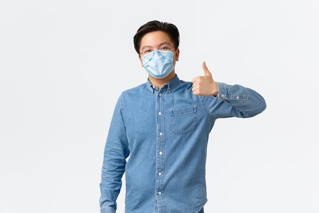 Covid-19, prevenzione del virus e concetto di distanza sociale sul posto di lavoro. sorridente ragazzo asiatico compiaciuto che indossa occhiali e maschera medica che mostra il pollice in su in segno di approvazione, raccomanda o approva qualcosa.