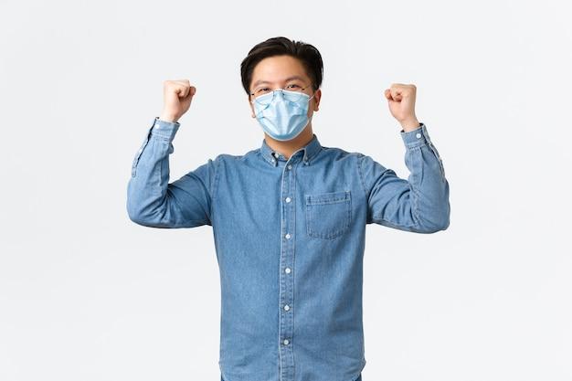 Covid-19, prevenzione del virus e concetto di distanza sociale sul posto di lavoro. l'uomo d'affari asiatico vincente di successo incoraggia un buon spirito di squadra, alzando le mani in segno di gioia, indossando una maschera medica