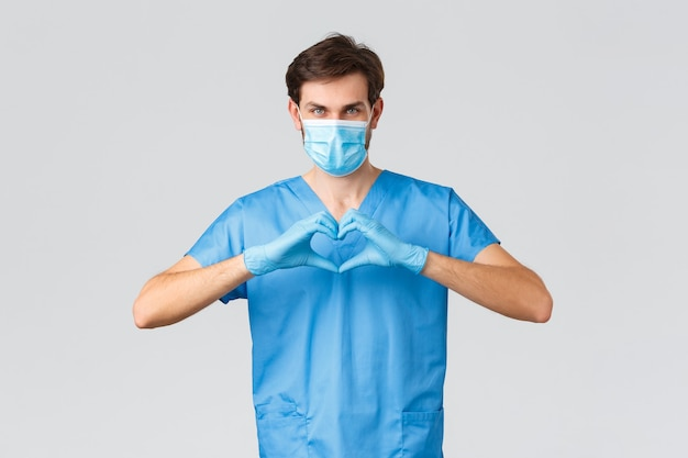 Covid-19, quarantena, ospedali e concetto di operatori sanitari. medico o infermiere serio e determinato in camice, maschera medica e guanti, che mostra il segno del cuore, si prende cura dei pazienti, chiede di restare a casa al sicuro