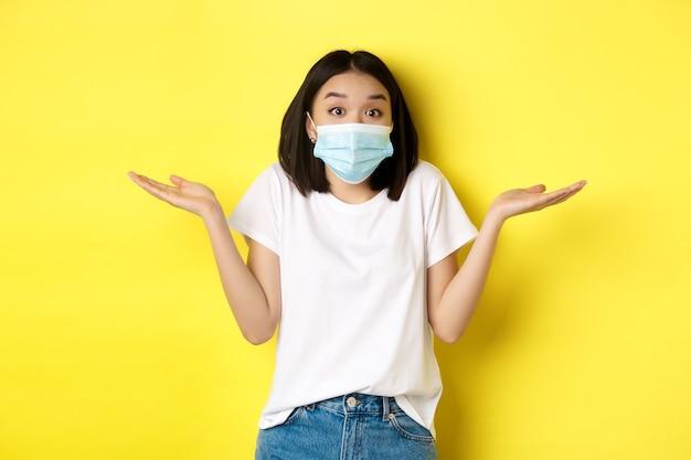 Covid-19, quarantena e concetto di allontanamento sociale. donna asiatica senza tracce in mascherina medica che scrolla le spalle, allarga le mani lateralmente all'oscuro, non sa niente, sfondo giallo.