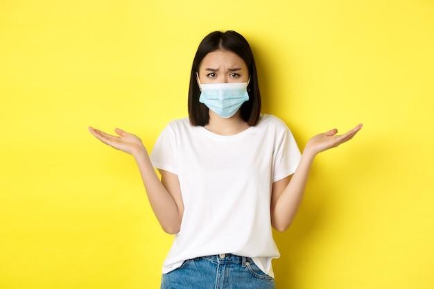 Covid-19, quarantena e concetto di allontanamento sociale. donna asiatica confusa in mascherina medica che scrolla le spalle, allarga le mani lateralmente all'oscuro, non sa niente, sfondo giallo.
