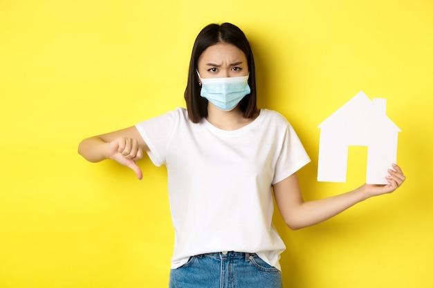 Covid-19 e concetto di bene immobile. donna asiatica delusa in maschera medica, che mostra il pollice verso il basso e il ritaglio della casa di carta, in piedi sconvolto su sfondo giallo.