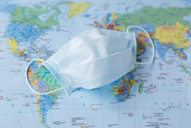 Covid-19, sars, mascherina chirurgica auricolare su uno sfondo di mappa del mondo. concetto di pandemia mondiale.
