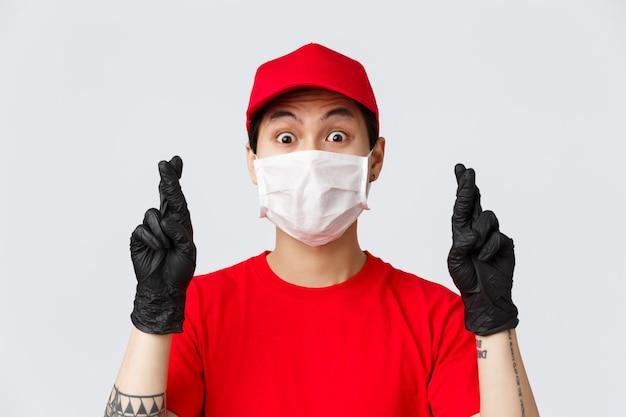 Covid-19, concetto di acquisti e consegne online auto-quarantena. nervoso corriere asiatico in maschera medica e guanti protettivi, indossa l'uniforme, incrocia le dita pregando, sperando che qualcosa appaghi