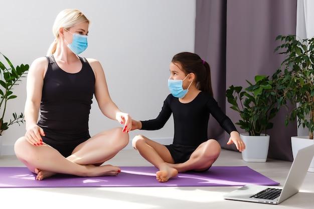Chiusura covid-19. madre e figlia in quarantena che fanno yoga al chiuso. madre e figlia che fanno meditazione durante il blocco. salute, esercizio fisico, stare a casa e prendersi cura di sé per l'isolamento del coronavirus.