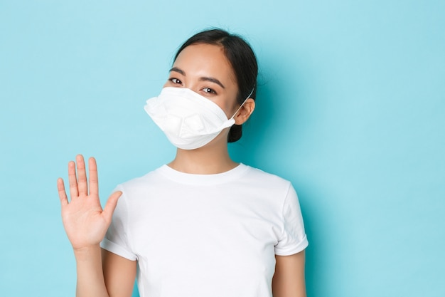 Covid-19, allontanamento sociale e concetto di pandemia di coronavirus. ragazza abbastanza asiatica sorridente allegra in respiratore medico che dice ciao, agitando la mano in ciao, gesto di saluto, parete blu chiaro