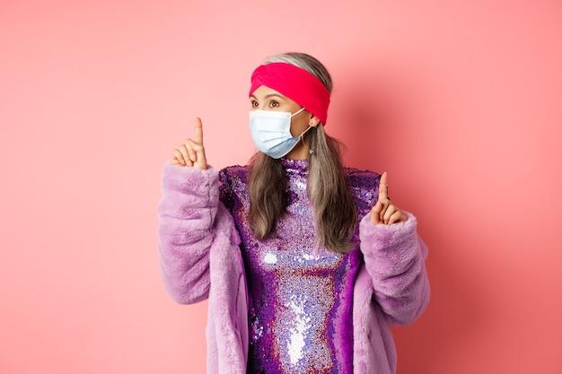 Covid-19, distanza sociale e concetto di moda. donna anziana asiatica elegante che balla e si diverte, indossa un respiratore medico e un vestito viola lucido, sfondo rosa