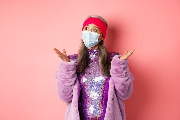 Covid-19, distanza sociale e concetto di moda. sorpresa e scioccata nonnina asiatica alla moda che guarda a sinistra, allarga le mani lateralmente confuse, in piedi su sfondo rosa