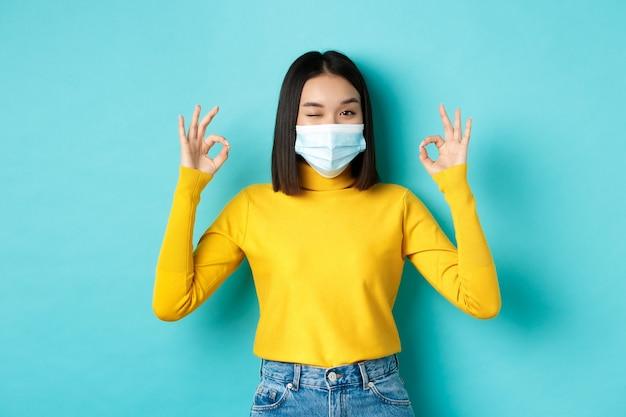 Covid-19, allontanamento sociale e concetto di pandemia. allegra ragazza asiatica in mascherina medica che mostra gesti giusti, strizzando l'occhio alla telecamera, mostrando approvazione, in piedi su sfondo blu.