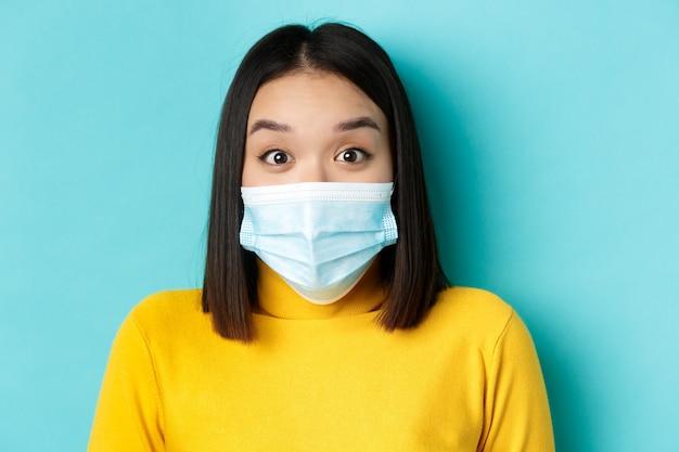 Covid-19, allontanamento sociale e concetto di pandemia. chiuda in su della donna asiatica sorpresa nella mascherina medica, solleva le sopracciglia e guarda stupito alla telecamera, sfondo blu.