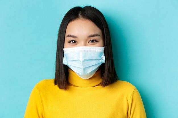 Covid-19, allontanamento sociale e concetto di pandemia. primo piano di giovane donna asiatica con corti capelli scuri, indossando maschera medica e sorridente con gli occhi, guardando speranzoso alla telecamera.