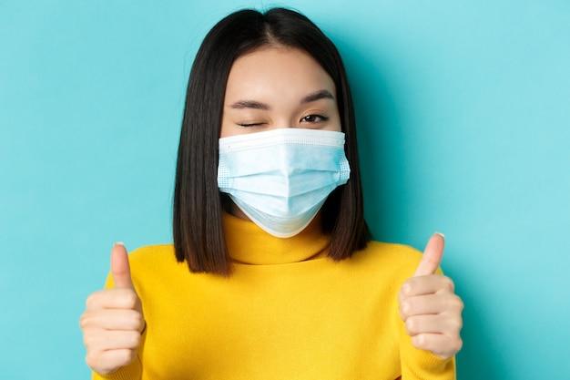Covid-19, allontanamento sociale e concetto di pandemia. ragazza asiatica carina in mascherina medica che strizza l'occhio alla macchina fotografica, mostrando i pollici in su, gesto di buon lavoro, lode bel lavoro, sfondo blu.
