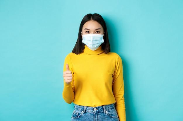 Covid-19, allontanamento sociale e concetto di pandemia. giovane donna in mascherina medica che mostra i pollici in su in approvazione, dicendo di sì, in piedi su sfondo blu.