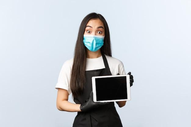 Covid-19, distanza sociale, piccola caffetteria e prevenzione del concetto di virus. barista asiatico in maschera medica e guanti che mostrano lo schermo del tablet digitale del cliente, con aria stupita