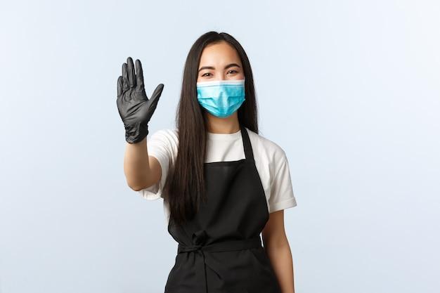 Covid-19, distanza sociale, piccola caffetteria e prevenzione del concetto di virus. barista femminile asiatica sorridente allegra e amichevole, cameriera che saluta i visitatori, salutando con la mano. Foto Premium