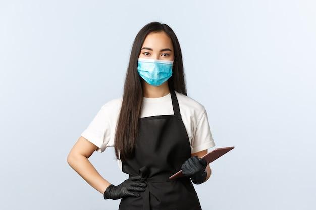 Covid-19, distanza sociale, piccola caffetteria e prevenzione del concetto di virus. barista femminile asiatico carino serio, cameriera che prende l'ordine del cliente con tablet digitale, indossa maschera medica e guanti.