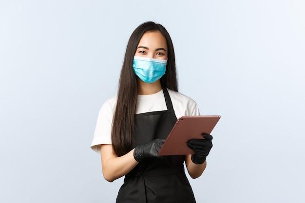 Covid-19, distanza sociale, piccola caffetteria e prevenzione del concetto di virus. sorridente barista asiatico carino, personale femminile del caffè che prende l'ordine con tablet digitale, indossa maschera medica e guanti