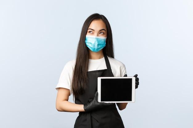 Covid-19, distanza sociale, piccola caffetteria e prevenzione del concetto di virus. la barista asiatica premurosa e soddisfatta, la proprietaria di un caffè in maschera medica e guanti mostrano lo schermo del tablet digitale