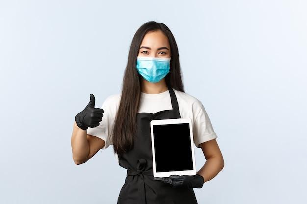 Covid-19, distanza sociale, piccola caffetteria e prevenzione del concetto di virus. il barista femminile asiatico sorridente soddisfatto, il proprietario del caffè o la cameriera mostrano il pollice in su e il tablet digitale, indossano una maschera medica.