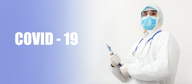 Testo covid-19 e portret del medico in tuta medica protettiva, rischio biologico, maschera facciale medico con stetoscopio scrive su tablet. concetto di assistenza medica coronavirus, covid, pandemia.
