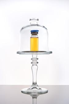 Concetto di presentazione del vaccino covid 19, dose di vaccino in fiala in cloche di vetro sulla superficie dello specchio, sfondo bianco, messa a fuoco selettiva