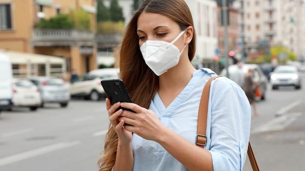 Covid-19 giovane donna che indossa la maschera ffp2 utilizzando uno smartphone in una strada cittadina