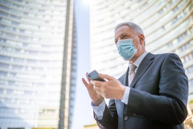 Concetto di covid, uomo d'affari anziano mascherato che usa il suo smartphone all'aperto in una città