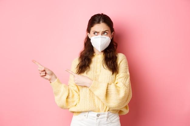 Covid, corona e concetto di allontanamento sociale. ragazza bruna confusa in respiratore medico avendo dubbi, indicando e guardando da parte lo spazio della copia a sinistra, in piedi contro il muro rosa.