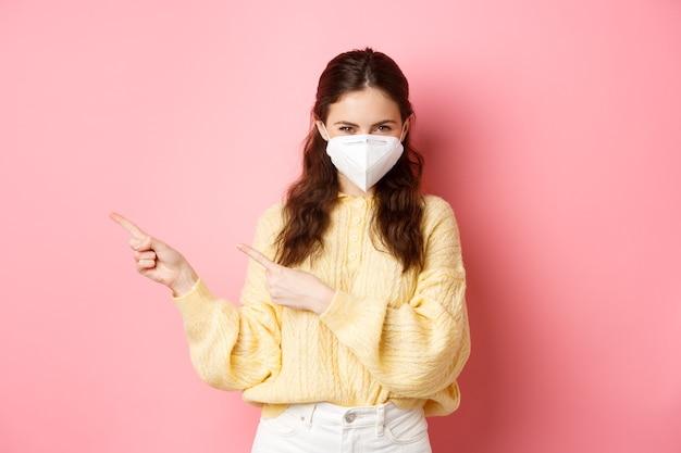 Covid, corona e concetto di allontanamento sociale. ragazza sorridente timida socchiudendo gli occhi pensieroso, puntando le dita da parte al banner del logo, indossando un respiratore medico durante la quarantena, muro rosa.