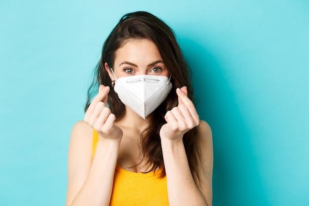Covid coronavirus e giovane donna carina che distanzia sociale che indossa una maschera per la salute e mostra i cuori delle dita