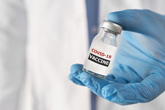 Concetto di vaccinazione contro il coronavirus covid in mano della veste bianca della fiala del barattolo di vetro del medico