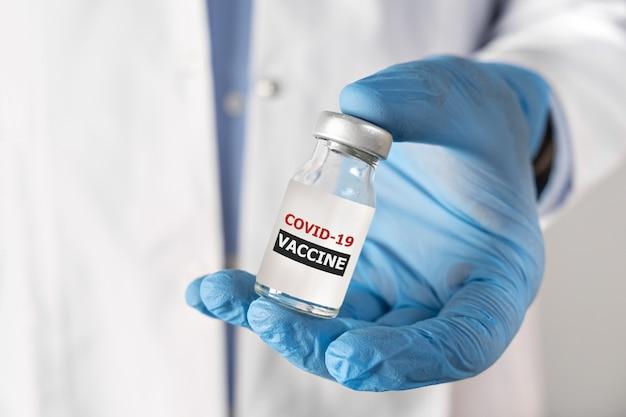 Concetto di vaccinazione contro il coronavirus covid in mano della fiala bianca del barattolo di vaccino in vetro medico e
