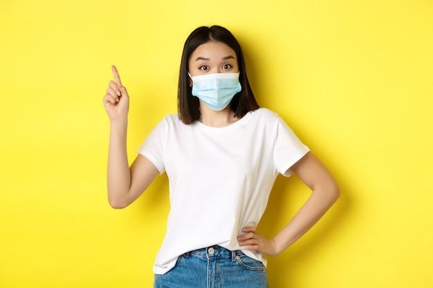 Covid, assistenza sanitaria e concetto di pandemia. modello femminile asiatico in mascherina medica e t-shirt bianca che punta il dito nell'angolo in alto a sinistra del logo, che mostra la promozione, sfondo giallo.