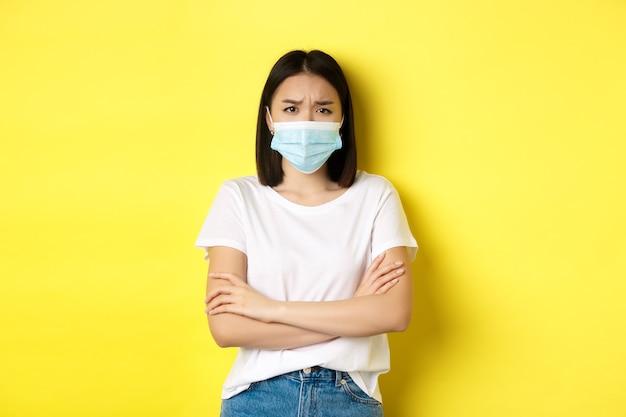Covid, assistenza sanitaria e concetto di pandemia. donna asiatica in maglietta bianca e maschera medica incrocia le braccia sul petto e sembra triste e delusa dalla telecamera