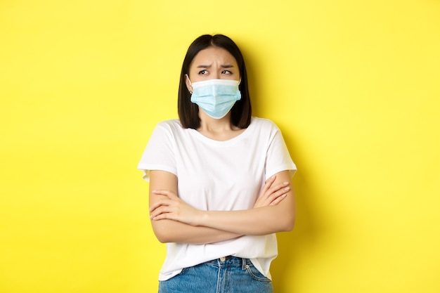 Covid, assistenza sanitaria e concetto di pandemia. donna asiatica in maglietta bianca e maschera medica incrocia le braccia sul petto e alza lo sguardo pensierosa e preoccupata.