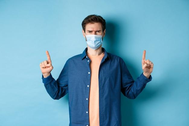 Covid e il concetto di assistenza sanitaria. uomo arrabbiato in maschera facciale che punta le dita verso l'alto, si sente deluso e sconvolto, in piedi su sfondo blu.