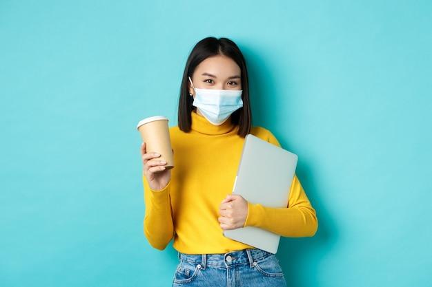 Covid, pandemia e concetto di allontanamento sociale. elegante donna asiatica che indossa una maschera medica, tenendo la tazza di caffè e laptop, andando a lavorare, in piedi su sfondo blu.