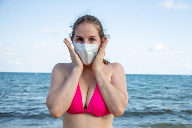 Covid viaggiando giovane ragazza caucasica in una maschera medica e in costume da bagno guarda paurosamente la spiaggia