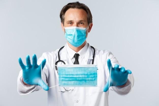 Gli operatori sanitari del virus covid e il concetto di vaccinazione medico in dpi allungano le mani e danno al paziente m...