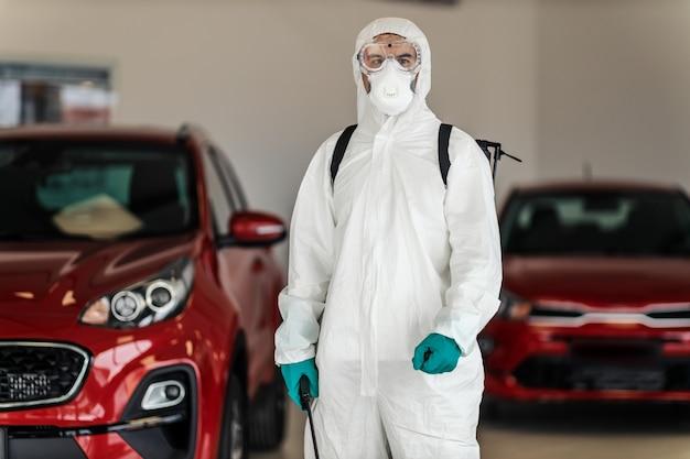 L'avviso di pericolo covid19 smette di diffondere un virus un professionista maschio in tuta protettiva impedisce