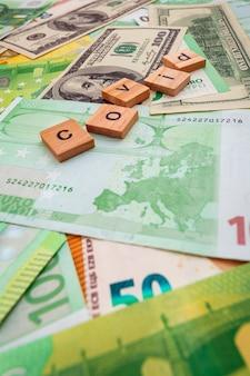 Iscrizione covid19 su cubi di legno sulla trama di dollari americani e banconote in euro
