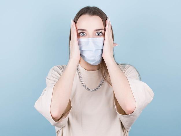 Covid19, allontanamento sociale, virus e concetto di stile di vita. una donna scioccata in una maglietta beige con una catena al collo e una mascherina medica
