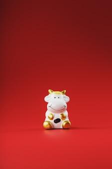 Figurina di mucca su uno sfondo rosso, concetto del nuovo anno