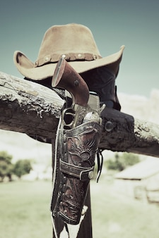 Pistola e cappello da cowboy all'aperto sotto la luce solare