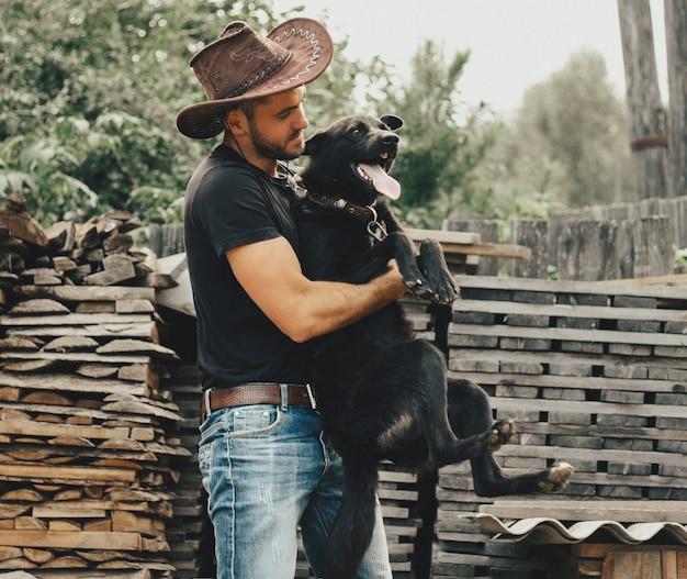 Il ragazzo del cowboy abbraccia la vita rurale del cane nero