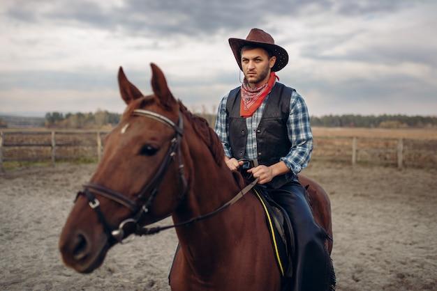 Cowboy in vestiti di cuoio che monta un cavallo in fattoria