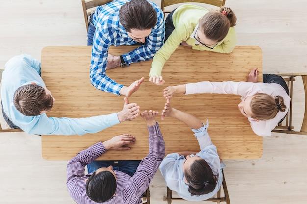 Colleghi che si danno il cinque seduti al tavolo dell'ufficio