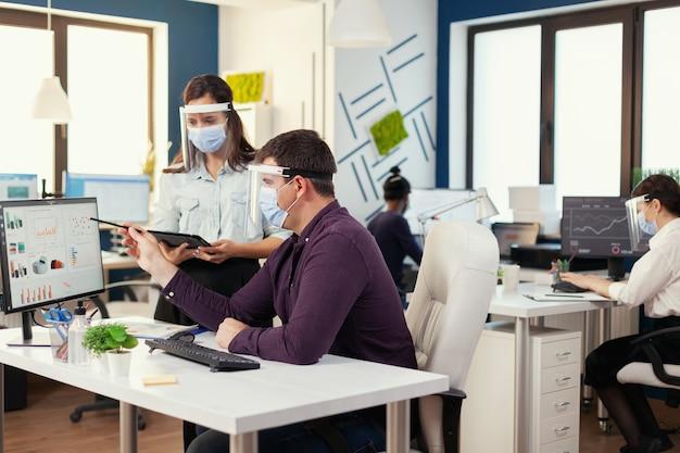 I colleghi che indossano la maschera per il covid19 si consultano sul posto di lavoro durante il covid19. squadra multietnica nel nuovo normale ufficio finanziario in una società aziendale digitando sul computer, prendendo appunti su tabl