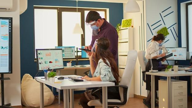 Colleghi con maschere di protezione che lavorano insieme sul posto di lavoro durante la pandemia. squadra multietnica nel nuovo normale ufficio finanziario in azienda aziendale digitando sul computer, prendendo appunti sul tablet.